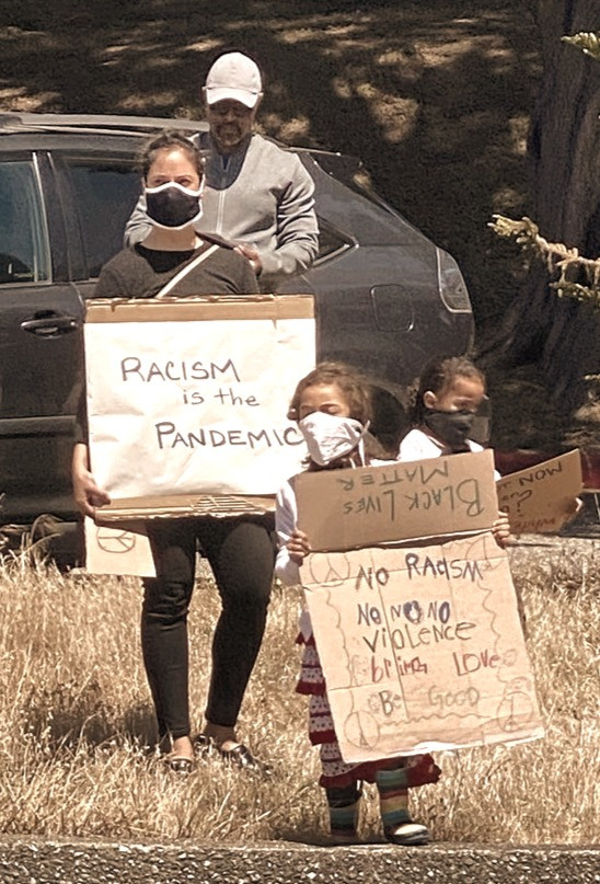 """Two children, a woman, and a man are walking toward the camera with cardboard signs saying """"racism is the pandemic,"""" """"Black Lives Matter,"""" and """"No Racism, No Violence"""""""