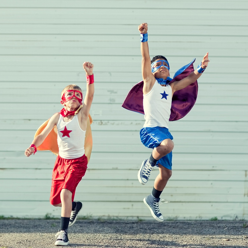 Two boys wearing superhero outfits and reaching toward the sky in an attempt to fly