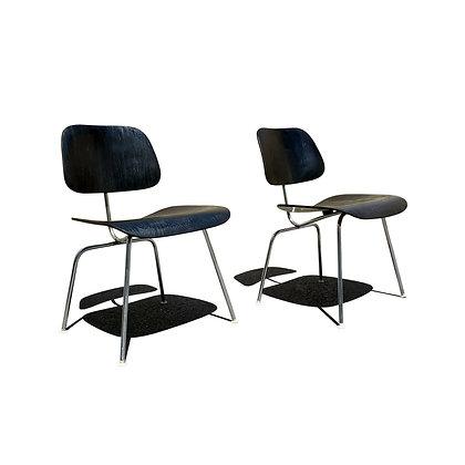 A black mid-century modern Eames DCM chairs