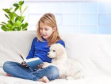 Little girl reading to dog