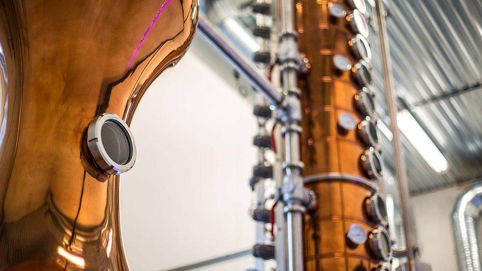 """In Zusammenarbeit mit der KotheKupferschmiede aus Eislingenhaben wir eine einzigartigeBrennblase entworfen. Wir haben die Möglichkeit diese als reine """"Pott-Still"""" laufen zulassen, wie wir es mit einigen unserer Whiskies tun. Andererseits können einige sogenannte Bödenin der Rektifikationssäuleaktiviert werden, wie Sie sie in unserer Gin-Produktion auffinden, oder manchmal nutzen wir alle15 Bödenvoll aus, um außergewöhnlich reinenWodka herzustellen."""