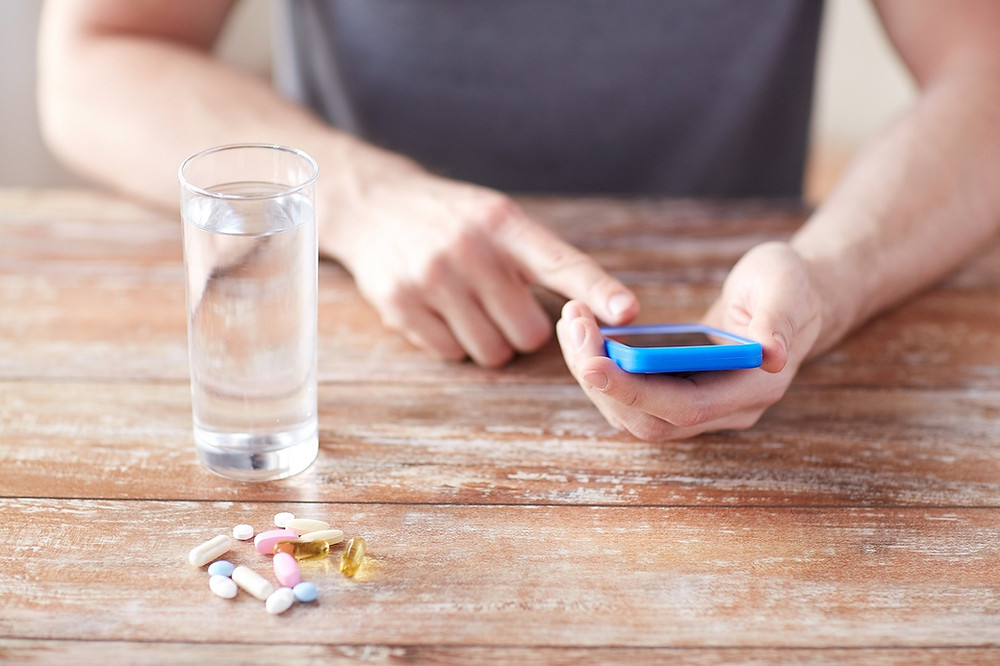 Person using phone to remember their prescribed pills, and how much to take.