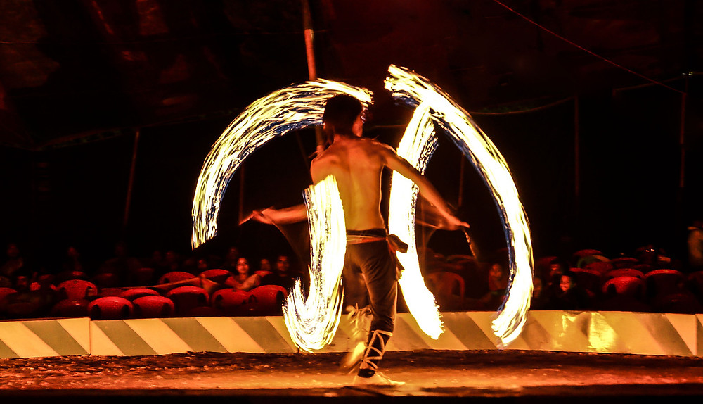 Agile man dancing while spinning fire torches.