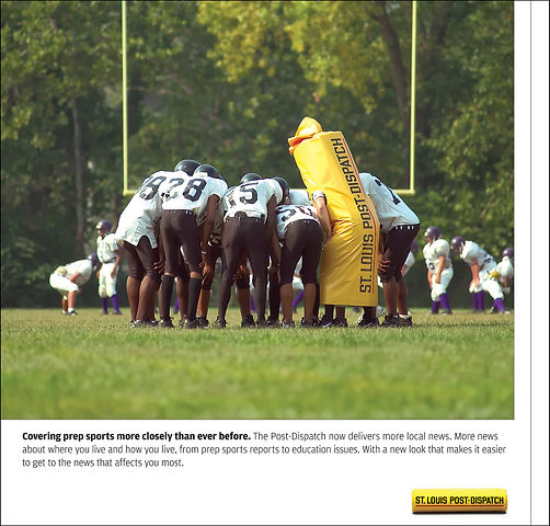 "St Lois Post Dispatch ""Yellowbag"" mascot in high school football huddle"