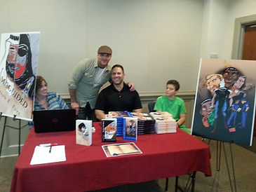 Jason posing for a shot with his illustrator, Caleb Rivera, a well as Jason's son - at a book signing at the local library.