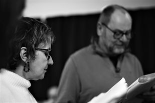Woman and man holding a play script