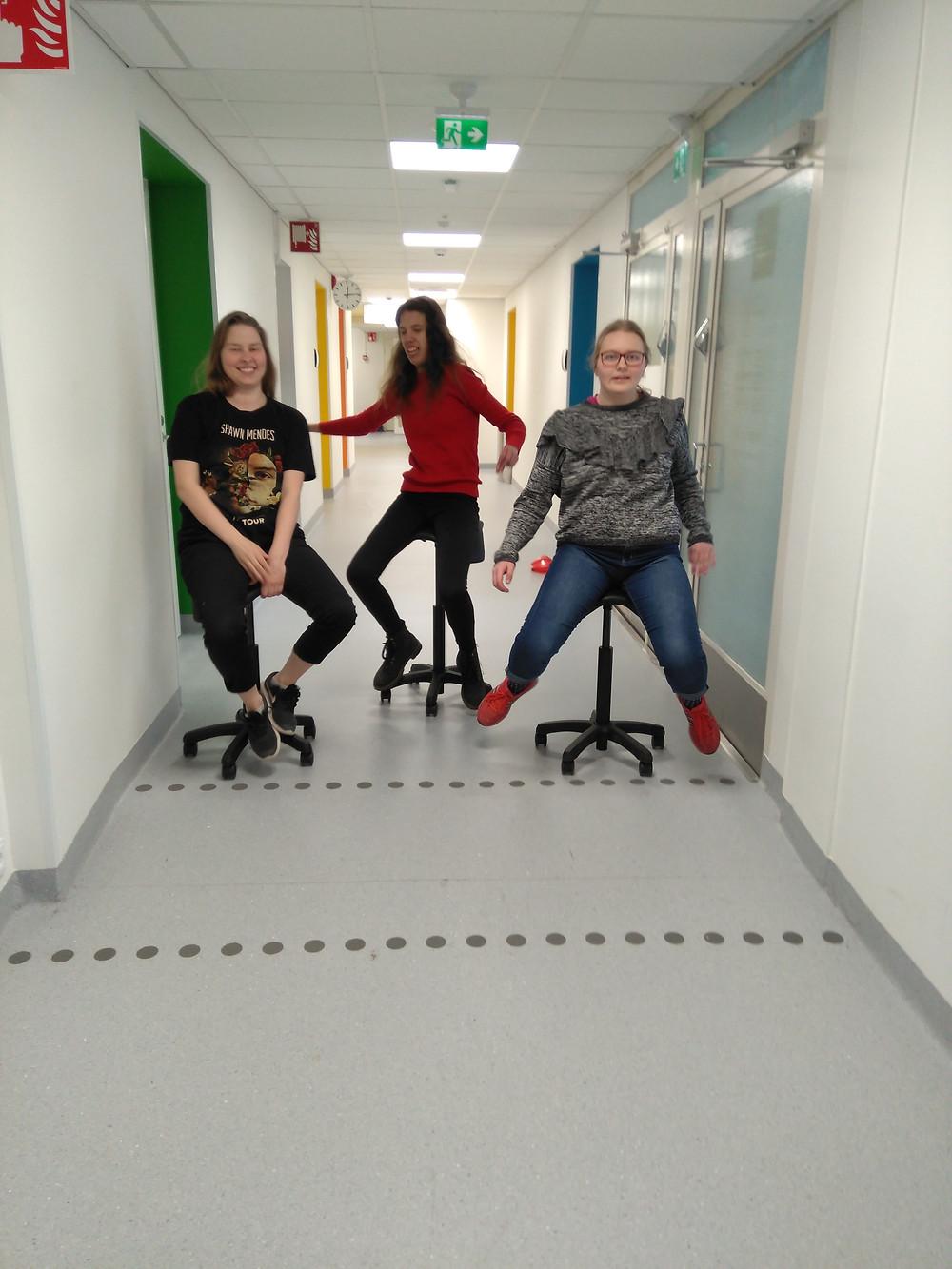 Kolme nauravaa tyttöä tuoleilla käytävällä