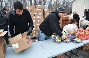 WLI volunteers Harris and Jacob assist with food distribution to local community,