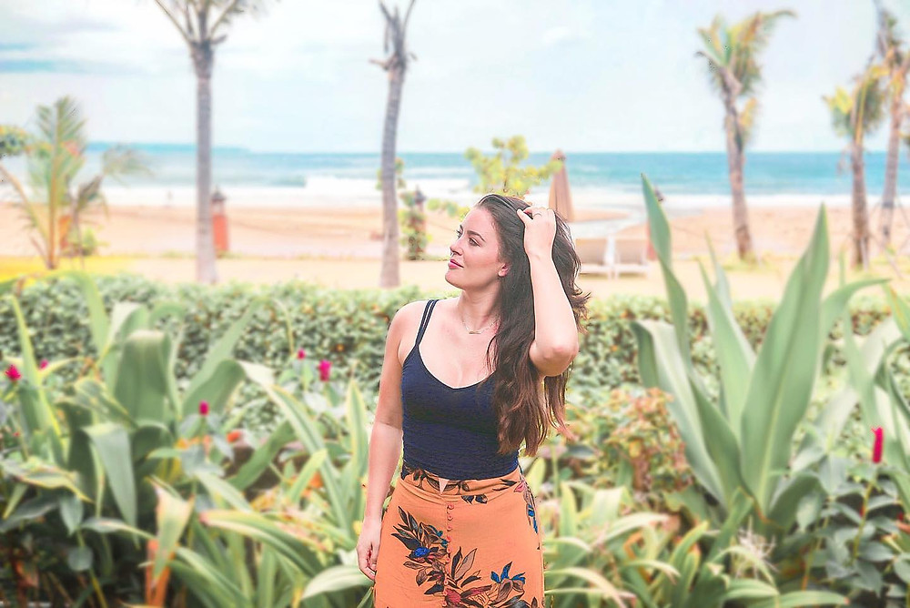 Brunette girl with long hair posing in front of the ocean in Bali Indonesia, wearing an orange flowery skirt and a green crop top. Sand, sea, palm trees