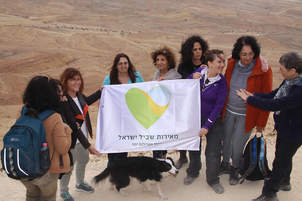נשים מטיילות יחד מאירות שביל ישראל מניפות דגל