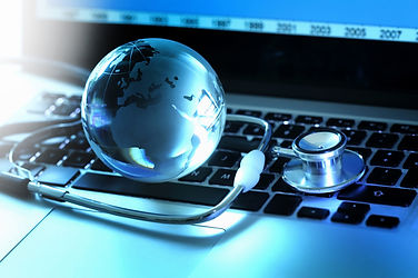 Stethoscope and globe on laptop keyboard