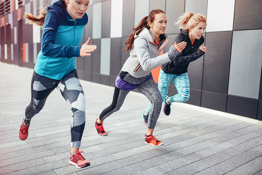 Three women running in colourful leggings past a building