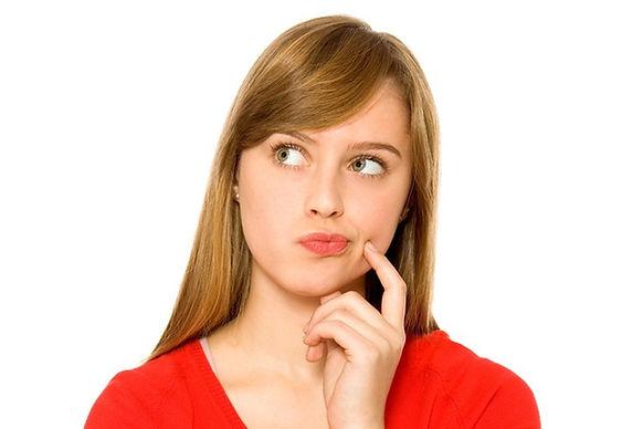 Девушка в красном выбирает между брекетами и элайнерами