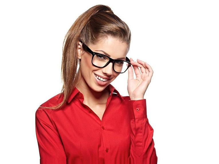 Улыбающаяся девушка в красном придерживает рукой очки