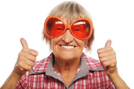 Пожилая женщина улыбается красивой белоснежной улыбкой и показывает два пальца вверх