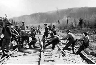 Black and white photo shows a group of railroad workers on one side of the tracks pulling on a rope while another group fixes a section of track.