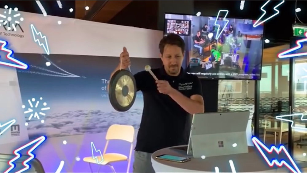 Mario Fallast rings the gong in front of a tablet