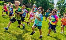 Picture of children in colorful tie-dye shirts running across the green lawn at the church.