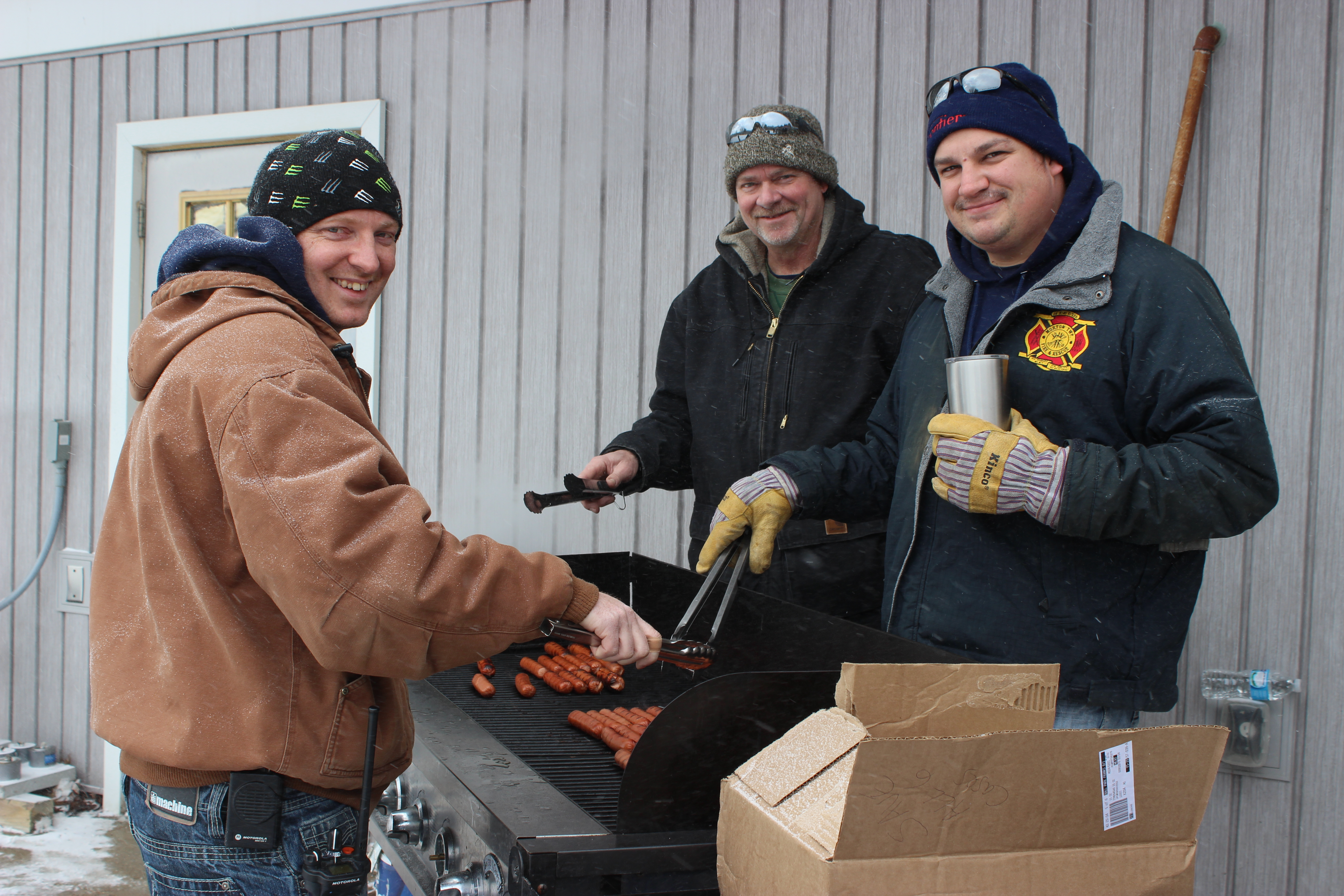 Firemen cooking hot dogs at the Winter Carnival!