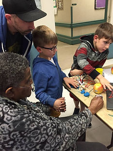 kids working on a science project with an elderly resident