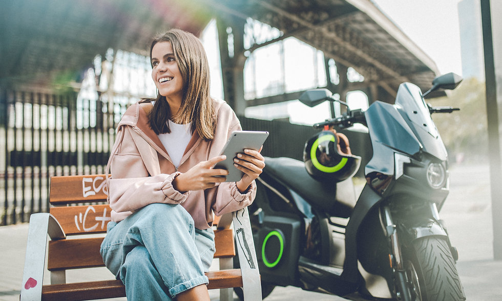 Woman looking at tablet device sitting next to a Silence e-moto scooter