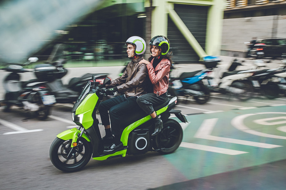 Man and woman riding a Silence S01 e-motor scooter on a road in an urban environment