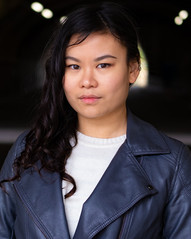 Mei, an Asian woman with long dark and slightly curly hair. She is wearing a grey leather jacket and looking in to the camera. She has a neutral facial expresion.