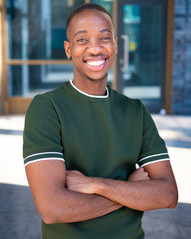 Kamari, a Black man with a lovely big smile looking in to the camera. He is wearing a green T-shirt and standing with his arms folded. He has short black hair where the sides and back styled shorter.