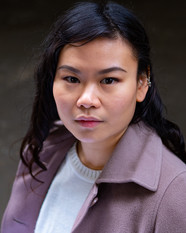 Mei, an Asian woman with long dark and slightly curly hair. She is wearing a white sweater and a dusty pink coat. Her head is looking slightly up to the camera with a neutral facial exression.