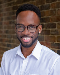 a close up of, Dwayne, a young slim Black man with a lovely black afro styled where the sides are short. He has a little bit of facial hair styled in a medium-thin line. He is wearing smart white plain shirt, brown glasses and looking in to the camera with a little smile. The background is a red-brown brick wall.