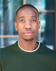 A close up headshot of Kamari. He is a Black man looking in to the camera with a neutral facial expression. He is wearing a green T-shirt. He has short black hair where the sides and back styled shorter.