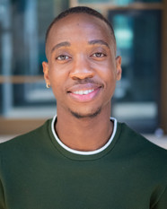 A close up headshot of Kamari. He is a Black man looking in to the camera with a small smile. He is wearing a green T-shirt. He has short black hair where the sides and back styled shorter.