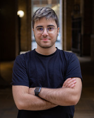 Alex is a Cypriot man with dark features, a labret piercing and a stubble. He is wearing a plain black t-shirt, glasses with metallic colour frame. He has a gentle smile and is looking straight in to the camera with arms crossed in front. The background is a blurred shaded area.