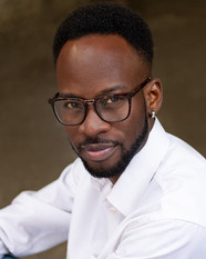 a close up of Dwayne, a young slim Black man with a lovely black afro styled where the sides are short. He is wearing smart white plain shirt, brown glasses and looking in to the camera with a little smile.