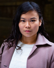 Mei, an Asian woman with long dark and slightly curly hair. She is wearing a white sweater and a dusty pink coat. Her head is looking straight in to the camera with a neutral facial exression.