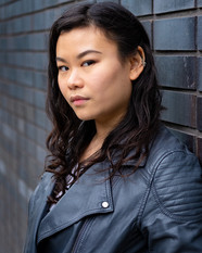 Mei, an Asian woman with long dark and slightly curly hair. She is wearing a grey leather jacket, her head is turned to the camera and she is looking in to it. She has a neutral facial expresion.