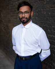 Shafi is a British asian man with dark and short facial hair. He has black hair parted on the side. He is wearing glasses, a white shirt buttoned up to the top and high waist dark blue trousers. He is looking in to the camera.