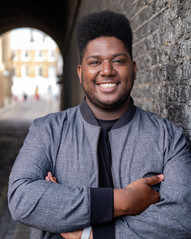 Alexis is a tall, Black and large man with a lovely smile and a tall black afro. The hair is styled short at the side. He is wearing a grey light jacket and a black t-shirt. He is leaning on a wall with crossed arms in this picture