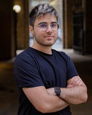 Alex is a Cypriot man with dark features, a labret piercing and a stubble. He is wearing a plain black t-shirt, glasses with metallic colour frame. He has a gentle smile and is looking straight in to the camera with arms crossed in front and body facing to the right. The background is a blurred shaded area.