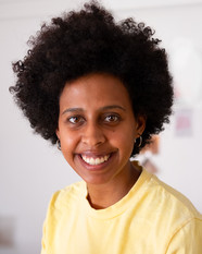 A headshot of my self. I am a Black slim woman with a small/medium size dark afro. I am wearing a yellow tshirt. I am looking in to the camera with a big smile.
