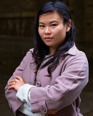Mei, an Asian woman with long dark and slightly curly hair. She is wearing a white sweater and a dusty pink coat. She is looking in to  the camera with slight smile. Her arms are crossed.