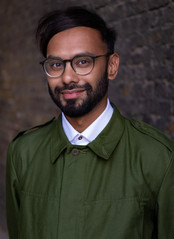Shafi is a British asian man with dark and short facial hair. He has black hair parted on the side. He is wearing glasses, a dark green jacket buttoned to the top and his white shirt's collar showing underneath the jacket. He is smiling gently looking in to the camera.