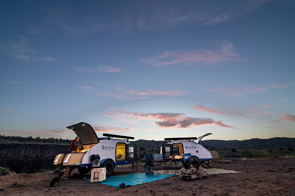 Two pindrop travel trailers in the desert at sunset with the back hatch open and a man cooking using the trailer's pull out two burner stove kitchen.