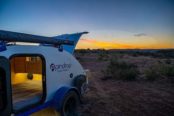 Pindrop travel trailer in the open desert at sunset with the kitchen hatch and cabin door open.