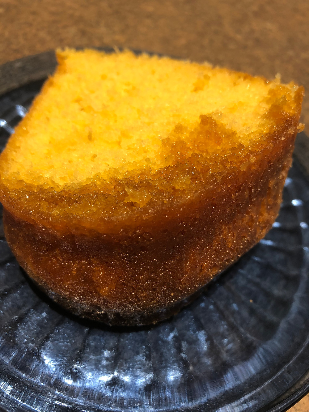 A yellow cake with brown glazed crust sits on a blue tinted plate, ready to eat.