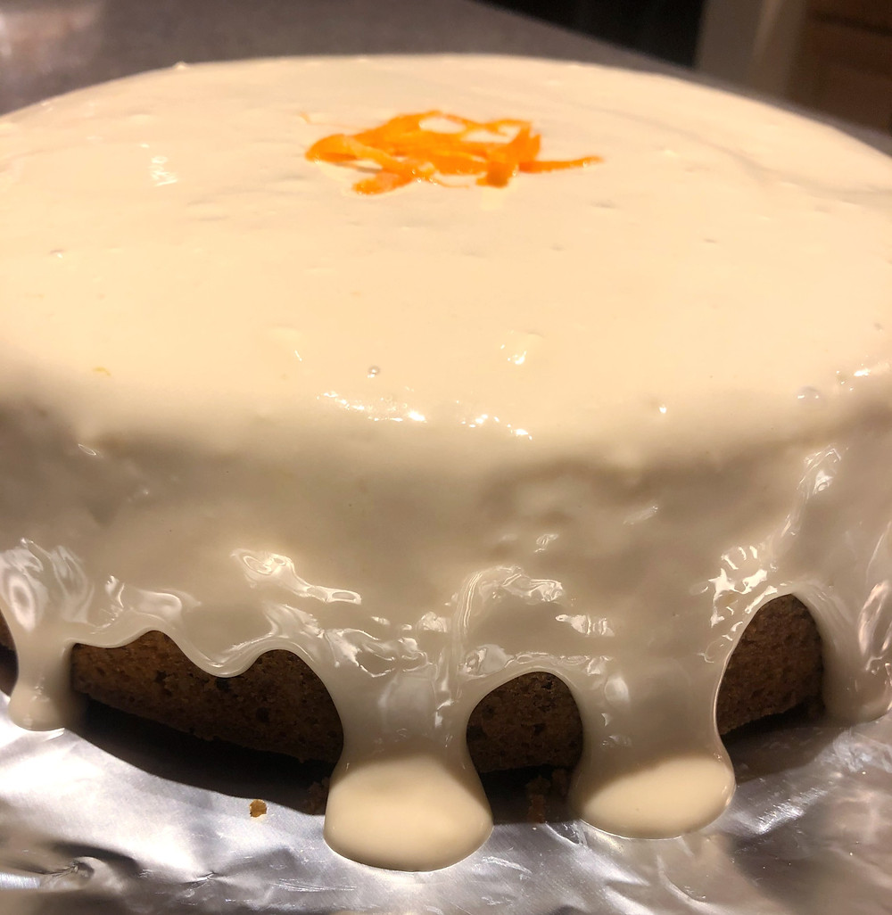 A round cake sits on a silver platter with white frosting dripping down edges. A small pile of orange carrot shavings sits in center of cake.
