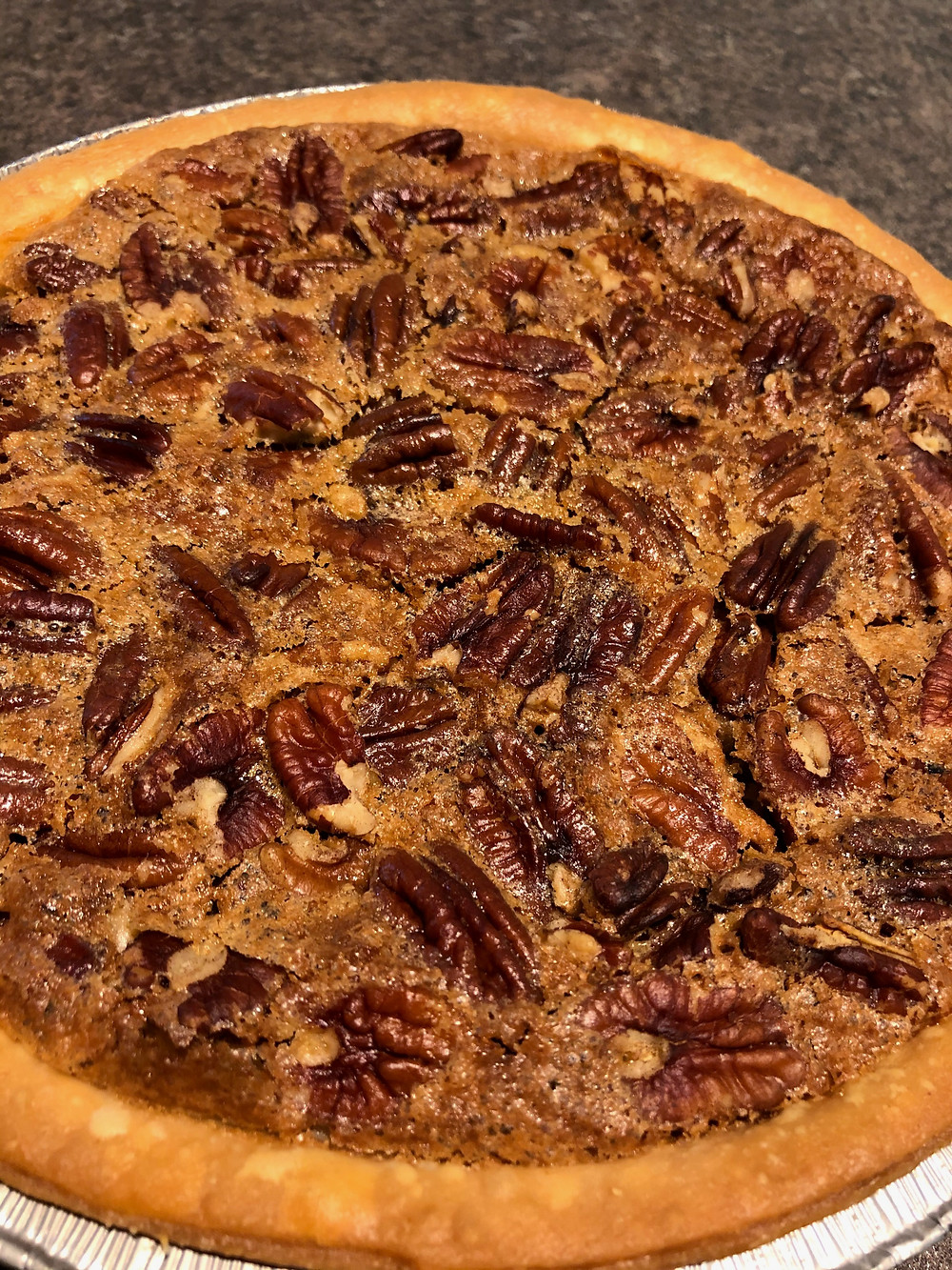 A golden pecan pie sits in a silver pan, ready to cut and serve.