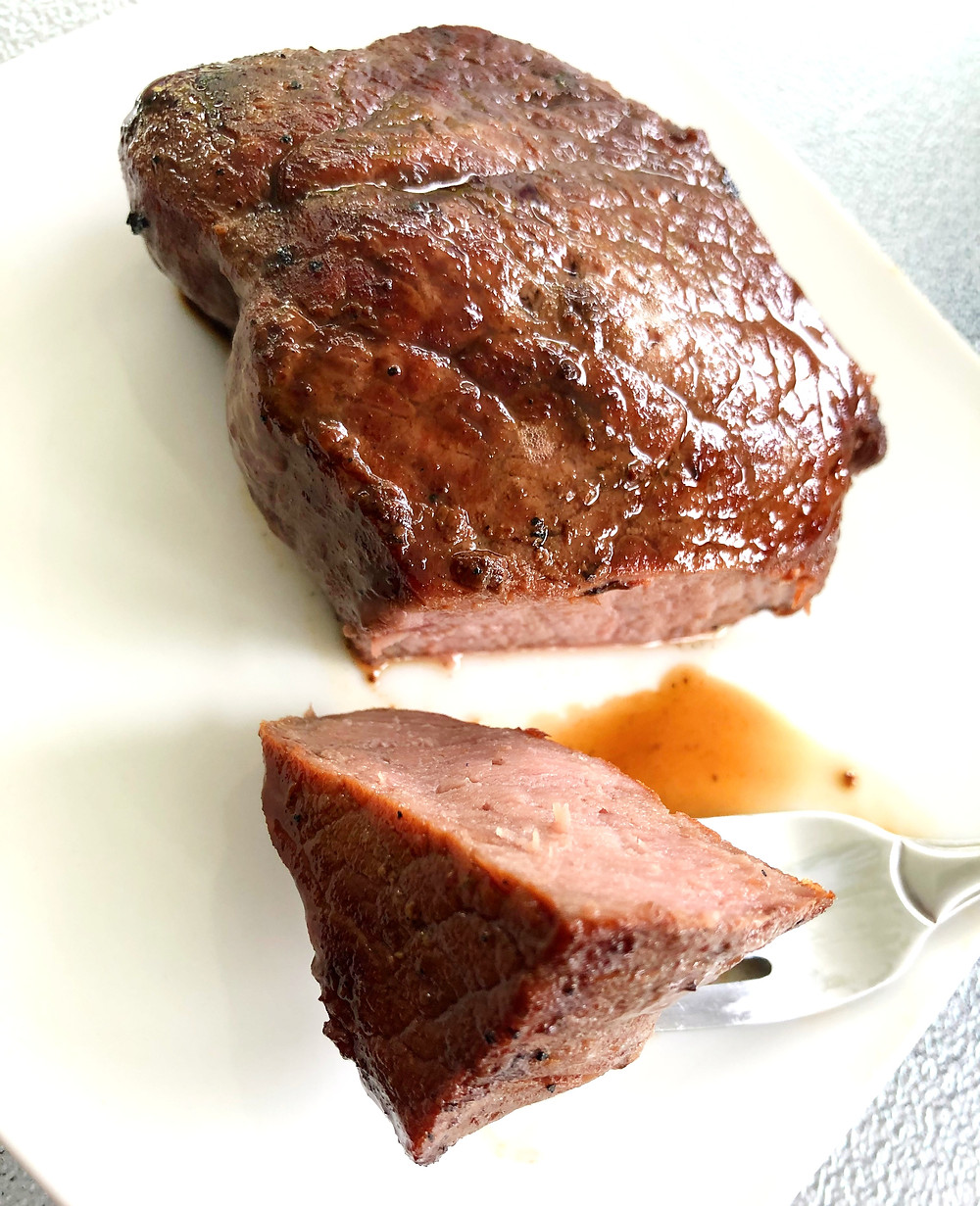 A grilled steak cut sits on a white plate, with a piece cut and ready to eat on a silver fork. Brown juices run onto white plate from the prepared meat.