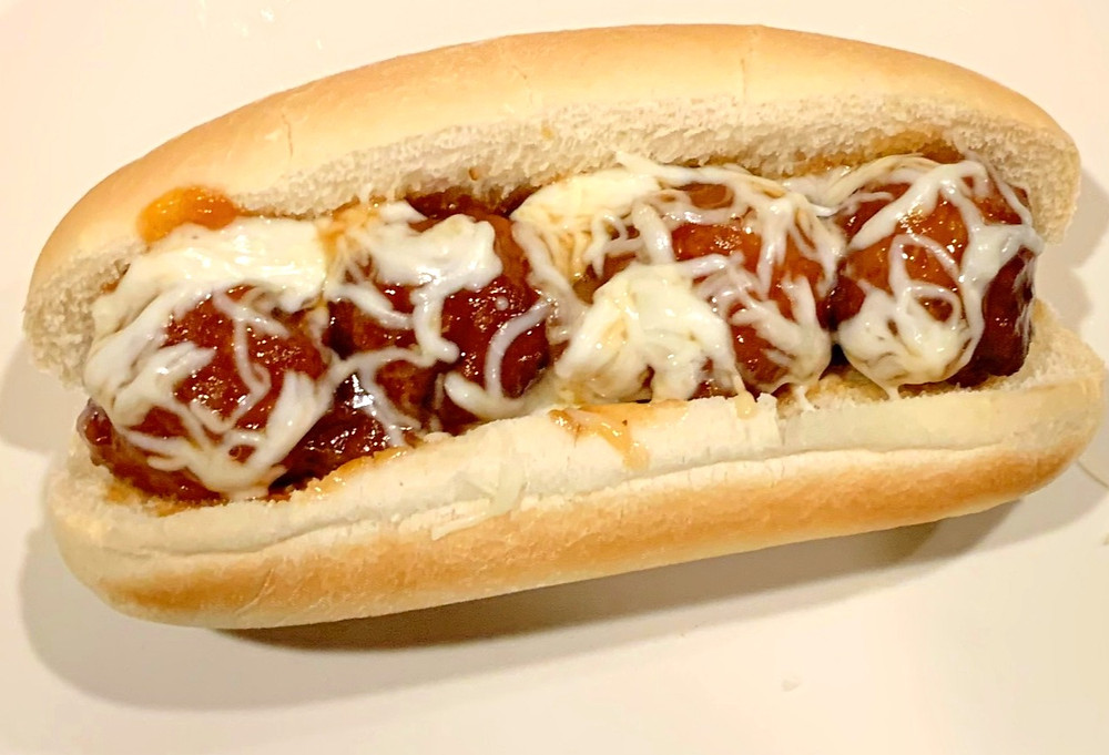 Four meatballs sit perched on a white hoagie roll and are topped with white melted shredded cheese.