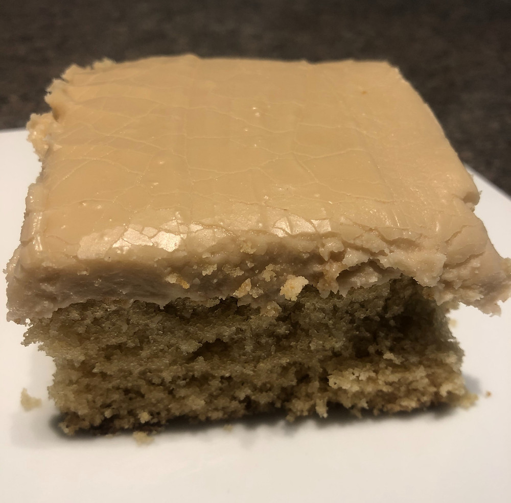 A square piece of light brown cake topped with thick tan frosting.